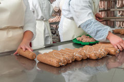 Close-up making sausages automatic process. Meat plant traditional sausage during the preparation Stock Photos