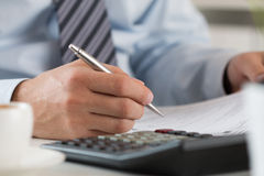 Close up of male accountant making calculations. Man writing something sitting at his office. Partnership agreement, contact signing, closing balance, making royalty free stock photography