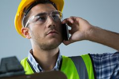 Male architect talking on mobile phone. Close-up of male architect talking on mobile phone Royalty Free Stock Photos