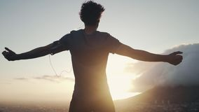 Male jogger with open arms looking at morning sunlight. Close-up of a male athlete standing on the top of the hill with his arms open overlooking the city at stock footage