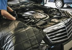 Close up of male auto mechanic working on engine in auto repair. Shop stock photography