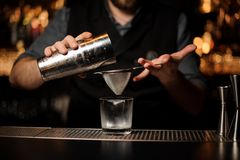 Close-up of bartender holding shaker and sieve. Close-up of male bartender holding steel shaker and sieve at bar counter stock photo