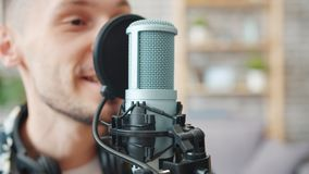 Close-up of male blogger talking in microphone recording podcast in studio. Close-up slow motion of male blogger talking in microphone recording podcast in stock video