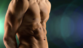 Close up of male bodybuilder bare torso. Sport, bodybuilding, strength and people concept - cclose up of male bodybuilder bare torso over dark background stock image