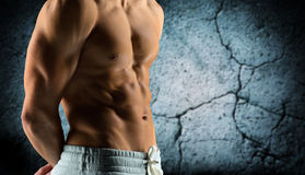 Close up of male bodybuilder bare torso. Sport, bodybuilding, strength and people concept - close up of male bodybuilder bare torso over concrete wall background royalty free stock image