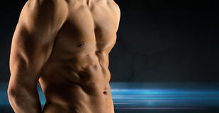 Close up of male bodybuilder bare torso. Sport, bodybuilding, strength and people concept - close up of male bodybuilder bare torso over dark background stock photography