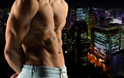 Close up of male bodybuilder bare torso. Sport, bodybuilding, strength and people concept - close up of male bodybuilder bare torso over night city background Royalty Free Stock Photography