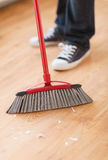 Close up of male brooming wooden floor Stock Photo