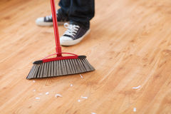 Close up of male brooming wooden floor Stock Image