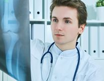 Close up portrait of young male doctor holding x-ray or roentgen image. Close up of male Caucasian doctor holding x-ray or roentgen image Royalty Free Stock Photo