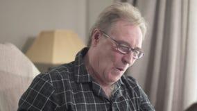 Close-up of male caucasian retiree laughing as watching photo album. Cheerful old man in eyeglasses enjoying recalling
