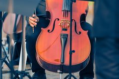 Close up of male cellist holding cello at an outdoor concert. During warm golden hour evening light, good for music or self interest theme concept stock images