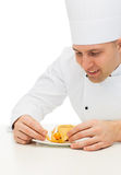 Close up of male chef cook decorating dessert Stock Images
