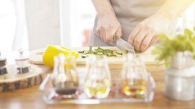 Male cooker`s hands slicing cucumbers on a wooden cooking board. Close up of male cooker`s hands cutting slicing cucumbers on a wooden kitchen board olive and Royalty Free Stock Image
