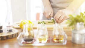 Male cooker`s hands slicing cucumbers on a wooden cooking board. Close up of male cookers hands cutting slicing cucumbers on a wooden kitchen board olive and Stock Photo