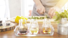 Male cooker`s hands slicing cucumbers on a wooden cooking board. Close up of male cookers hands cutting slicing cucumbers on a wooden kitchen board olive and Royalty Free Stock Image