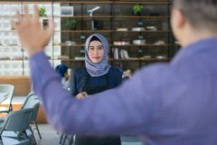 Male costumer calling for hijab female cafe waiters, ready for order. Close up male costumer raising hand calling for hijab female cafe waiters, ready for order royalty free stock image