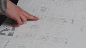 Close up of male design engineer sits at the desk, blueprints laying on his desk