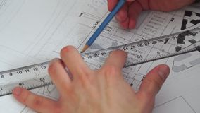 Close up of male design engineer sits at the desk in her office, blueprints laying on his desk