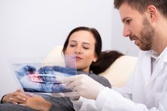 Male Doctor Explaining X-ray To Patient stock photos