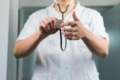 Bright close up of male doctor in uniform with stethoscope. Listening and holding stethoscope. Copy space stock images