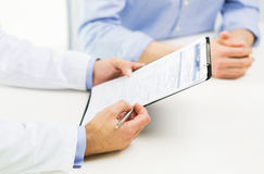 Close up of male doctor and patient with clipboard. Medicine, health care, people and prostate cancer concept - close up of f male doctor and patient hands with stock images