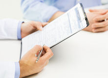 Close up of male doctor and patient with clipboard Royalty Free Stock Image