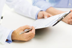 Close up of male doctor and patient with clipboard. Medicine, health care, people and prostate cancer concept - close up of f male doctor and patient hands with royalty free stock photo