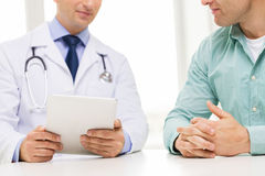 Close up of male doctor and patient with tablet pc Stock Photos