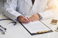 Male doctor sitting at desk and writing notes on clipboard royalty free stock image