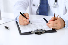 Close up of male doctor is sitting at the table and filling up medical history form.  stock images