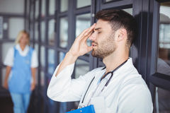 Close-up of male doctor suffering from headache. While standing at hospital Royalty Free Stock Photos