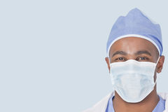 Close-up of a male doctor wearing facemask over light blue background Royalty Free Stock Photography