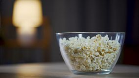 Close up of male eating popcorn from the bowl on table, unhealthy food addict. Stock footage stock video
