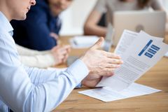 Close up of male employee reading paperwork report at meeting stock photos