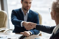 Close up of business partners handshaking at briefing. Close up of male employee shaking hand of female colleague greeting at business meeting, workers handshake stock photos
