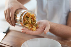 Close up of male emptying jar with colorful pasta Stock Photos