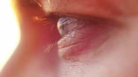 Extreme macro close up of male eye watching sunset by the sea. Enjoying nature in slow motion, HD. 1920x1080