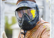 Close-up of male face in paintball mask with big splash. Outdoors stock photography