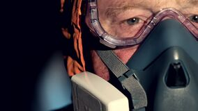 Male face in a respirator and antibacterial suit in a dark room