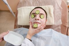 Close-up of male face with white mask and cucumbers. Facial treatment for man in beauty clinic. Close-up of male face with white mask and cucumbers Royalty Free Stock Images