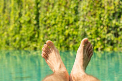 Close up of male feet over resort swimming pool Royalty Free Stock Photography