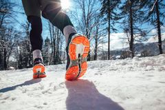 Close up of male feet running along winter road. And snow Royalty Free Stock Photography