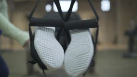 Close-up of male feet in sneakers hanging on TRX straps. Blurred young athletic man exercising in gym with help of