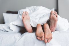 Young man and woman having fun under quilt in bedroom. Close up of male and female bare feet. Young couple is luxuriating in bed covered by white blanket. Focus Royalty Free Stock Photography
