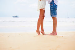 Close up male and female feet on the sand. With the sea and a boat at the background Stock Photography