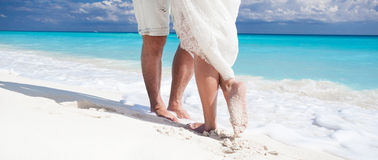 Close up male and female feet on the sand. Close up male and female feet on white sand, kissing Royalty Free Stock Photo