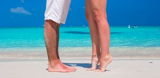 Close up male and female feet on white sand. Beach Royalty Free Stock Photography