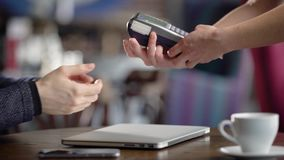 Close up of male and female hands doing process of cashless payment in restaurant. Waitress giving to customer POS stock video footage
