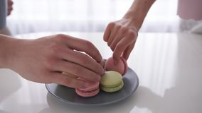 Close up of male and female hands holding cups of coffee with macaroons are on table. Close up of male and female hands holding cups of coffee. Couple is sitting stock video footage